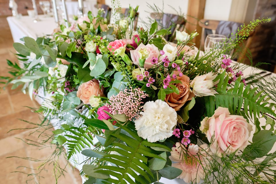 The Head Table at George & Tonia's Swancar Farm, Nottinghamshire Wedding. Flowers by Sassy Blooms, Leicestershire.