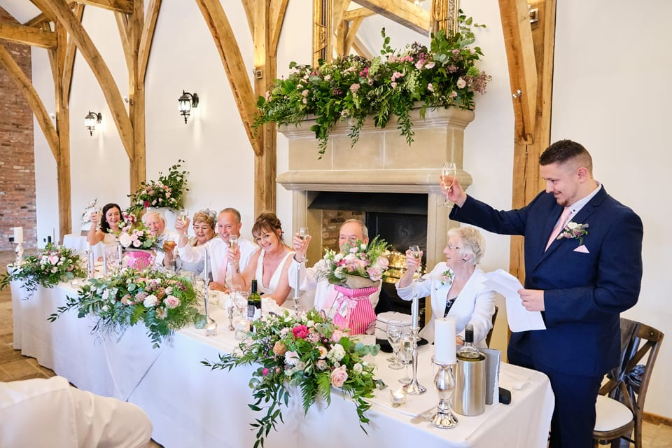A toast at the Head Table. George & Tonia's Swancar Farm, Nottinghamshire Wedding. Flowers by Sassy Blooms, Leicestershire.